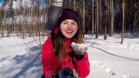 La muchacha turística feliz joven sopla la nieve de las palmas almacen de metraje de vídeo