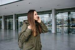 La muchacha turística hermosa joven en el aeropuerto o cerca del centro comercial o de la estación llama un taxi o hablar en una  Foto de archivo