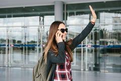 La muchacha turística hermosa joven en el aeropuerto o cerca del centro comercial o de la estación llama un taxi o hablar en una  Fotografía de archivo libre de regalías