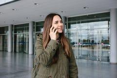 La muchacha turística hermosa joven en el aeropuerto o cerca del centro comercial o de la estación llama un taxi o hablar en una  Fotografía de archivo
