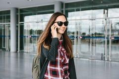 La muchacha turística hermosa joven en el aeropuerto o cerca del centro comercial o de la estación llama un taxi o hablar en una  Imagenes de archivo