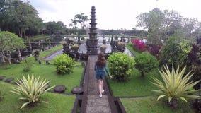 La muchacha turística joven va a una fuente hermosa en el palacio hindú Tirta Gangga del agua del Balinese metrajes