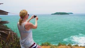 La muchacha turística lleva imágenes de un paisaje marino con una isla el mar Viaje y turismo en las islas tropicales metrajes