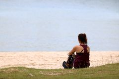 La muchacha turística que se relaja en la playa disfruta de una vista al mar Foto de archivo