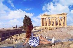 La muchacha turística se vistió en los colores de la bandera de Grecia que miraban Parthenon Foto de archivo