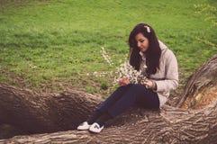 La muchacha turca hermosa joven que sostiene la cereza de la primavera florece y que se sienta en un árbol Foto de archivo