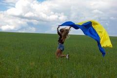 La muchacha ucraniana hermosa en una camisa de tela escocesa y un dril de algodón del cortocircuito pone en cortocircuito Imagenes de archivo