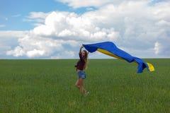 La muchacha ucraniana hermosa en una camisa de tela escocesa y un dril de algodón del cortocircuito pone en cortocircuito Fotos de archivo
