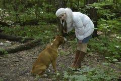 La muchacha, un mosquito y un perro en el bosque Fotos de archivo