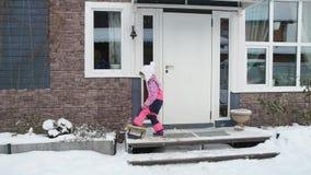 La muchacha, un niño limpia los zapatos de nieve y entra en la casa almacen de video