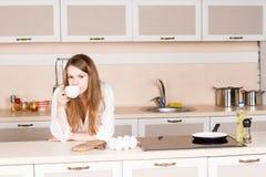 La muchacha una camisa de los hombres blancos está bebiendo codos del té en la tabla en cocina la mañana Imagen de archivo libre de regalías