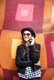 La muchacha urbana sonriente utiliza el teléfono elegante con sonrisa en su cara El retrato del gir de moda que lleva un estilo d Imagen de archivo libre de regalías