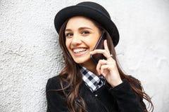 La muchacha urbana sonriente utiliza el teléfono elegante con sonrisa en su cara El retrato del gir de moda que lleva un estilo d Fotos de archivo