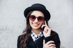La muchacha urbana sonriente utiliza el teléfono elegante con sonrisa en su cara El retrato del gir de moda que lleva un estilo d Fotos de archivo libres de regalías