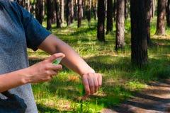 La muchacha utiliza el espray contra mosquitos Imágenes de archivo libres de regalías