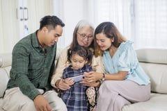 La muchacha utiliza el teléfono con los padres y la abuela fotos de archivo