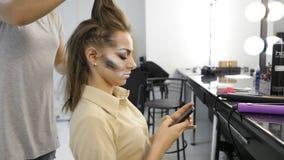 La muchacha utiliza el teléfono elegante en estudio de la moda mientras que trabajo del peluquero sobre el pelo del cliente almacen de video