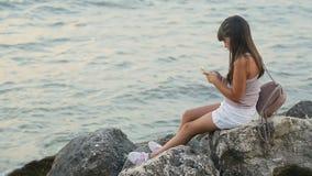 La muchacha utiliza el teléfono en el mar metrajes