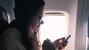 La muchacha utiliza el vuelo del rato del smartphone almacen de metraje de vídeo