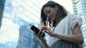 La muchacha utiliza Internet en un texto que mecanografía del smartphone en la calle contra la perspectiva de rascacielos en el  almacen de metraje de vídeo