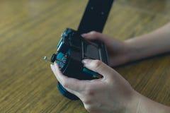 La muchacha utiliza la cámara retra Fotografía de archivo libre de regalías