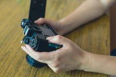 La muchacha utiliza la cámara retra Fotos de archivo libres de regalías