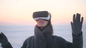 La muchacha utiliza los vidrios de la realidad virtual en el invierno en la calle almacen de metraje de vídeo