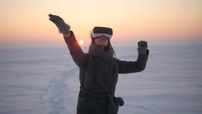 La muchacha utiliza los vidrios de la realidad virtual en el invierno en la calle almacen de video