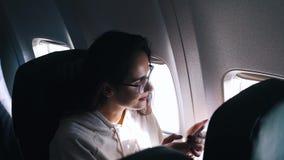 La muchacha utiliza un smartphone dentro del avión almacen de metraje de vídeo