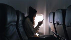 La muchacha utiliza un smartphone dentro del avión metrajes