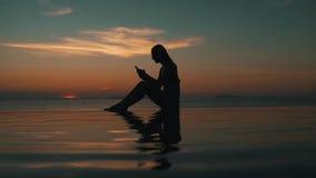 La muchacha utiliza un smartphone en la puesta del sol por el océano almacen de video