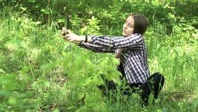 La muchacha utiliza una tableta en el bosque metrajes