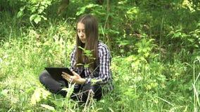 La muchacha utiliza una tableta en el bosque Imagen de archivo