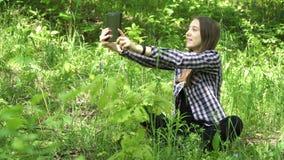 La muchacha utiliza una tableta en el bosque Fotografía de archivo