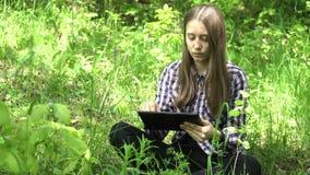La muchacha utiliza una tableta en el bosque almacen de video