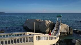 La muchacha va abajo en el puente contra paisaje marino imponente almacen de metraje de vídeo