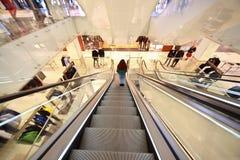 La muchacha va abajo en una escalera móvil Fotografía de archivo libre de regalías