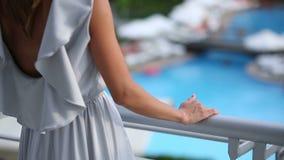La muchacha va al balcón delante de sus hermosas vistas de las ofertas del hotel metrajes