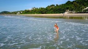La muchacha va al mar contra orilla tropical con las palmas