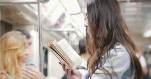 La muchacha va al subterráneo y lee un libro almacen de video