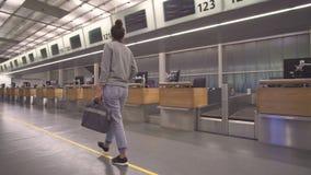 La muchacha va al terminal para el registro con un bolso metrajes