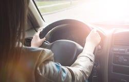 La muchacha va detr?s de la rueda de un coche, manos en el volante Conducci?n de un coche grande fotos de archivo libres de regalías