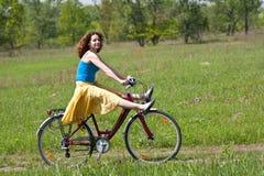 La muchacha va en bicicleta Imágenes de archivo libres de regalías