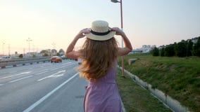 La muchacha va en el camino con una maleta Cerca de la carretera y de muchos coches almacen de video