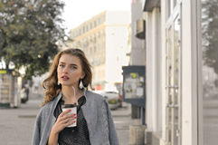 La muchacha va en la acera y el café de consumición Foto de archivo libre de regalías