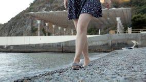 La muchacha va en las pequeñas piedras en la playa almacen de metraje de vídeo