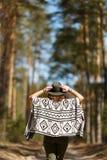 La muchacha va en un callejón del bosque vestido en poncho indio imagen de archivo