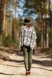 La muchacha va en un callejón del bosque vestido en poncho indio imagenes de archivo