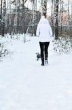 La muchacha va en un sendero en bosque del invierno Fotografía de archivo