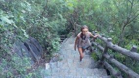 La muchacha va encima de las escaleras viejas en la montaña cubierta con la selva almacen de metraje de vídeo